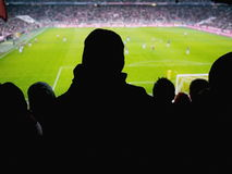 Silhouettes of fans on soccer game Royalty Free Stock Images