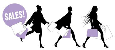 Silhouettes of fashionable women with shopping bags walking on the street Royalty Free Stock Images