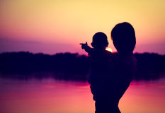 Silhouettes of Father and Baby Watching Sunset. By the Lake.  Family Concept. Toned Photo with Copy Space Stock Photography