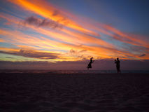 Silhouettes of father and daughter on the beach at Stock Images