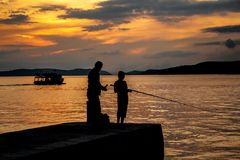 Silhouettes of father and his son fishing on sea Royalty Free Stock Photography