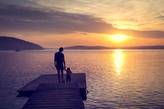 Silhouettes of Father with His Son by the Sea. Silhouettes of Young Father with His Little Baby Standing on the Pier and Watching Sunset by the Sea. Happy Family Stock Photos