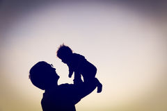 Silhouettes of father and little baby playing at sunset Stock Photography