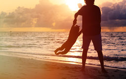 Silhouettes of father and little daughter playing Stock Photography