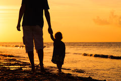 Silhouettes of father and little daughter walking Stock Photos