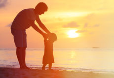 Silhouettes of father and little daughter walking Stock Photography