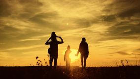 Silhouettes of father, mother and children hiking. Baby sits on the shoulders of his father. Hiking backpackers trekking. Mountains summer. Young family on stock video footage