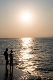 Silhouettes of father and son fishing. Sunset view Stock Photo