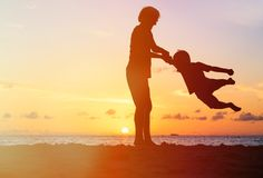 Silhouettes of father and son having fun at sunset Stock Photography