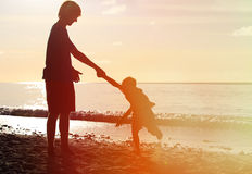 Silhouettes of father and son having fun at sunset Royalty Free Stock Photography