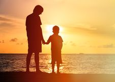 Silhouettes of father and son holding hands at Stock Image