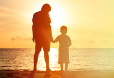 Silhouettes of father and son holding hands at. Sunset sea Stock Photography