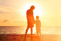 Silhouettes of father and son holding hands at Stock Photos
