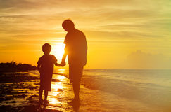 Silhouettes of father and son holding hands at Royalty Free Stock Photos