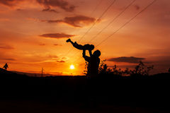 Silhouettes of father and son sunset background Stock Photography