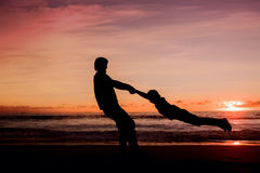 Silhouettes of father spinning his son around on Royalty Free Stock Photos
