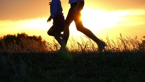 Silhouettes of feet of two children running against the sunset background. Happy brothers play catching up with each other. Slow motion stock footage