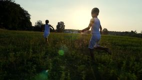 Silhouettes, figures of children, boy and girl are running, having fun, against the background of the sun, at sunset in stock footage
