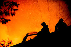 Silhouettes of firemen on a roof of a burning house. Silhouettes of firemen on the roof of a burning house Stock Photos
