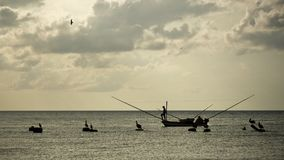 Silhouettes of fisherman on small fishing boat, with neotropic c royalty free stock photos