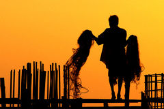 Silhouettes of Fishermen. On the beach at sunset Royalty Free Stock Images