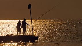 Silhouettes of fishermen on sea sunset background.  Royalty Free Stock Image