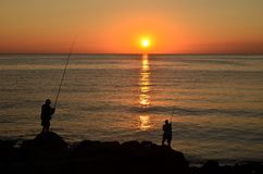Silhouettes of fishers on sea cliff at sunrise royalty free stock image