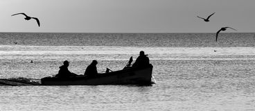 Silhouettes of fishers Royalty Free Stock Photos