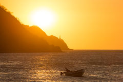 Silhouettes of fishers in Taganga bay with sunset Stock Photos