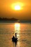 Silhouettes of fishing canoe on Niger River Stock Photography