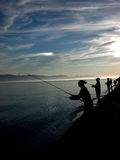 Silhouettes fishing on the shore. Silhouettes of people fishing for salmon along the shore with a sundog Stock Images