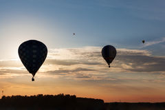 Silhouettes of flying balloons on the sunset sky Stock Photography
