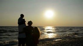 Silhouettes foncées des parents avec deux filles regardant le coucher du soleil près de la mer clips vidéos