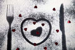 Silhouettes of fork, knife and hearts on the flour on a black ba Royalty Free Stock Photos