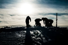 Silhouettes of four snowboarders Stock Photos