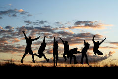 Silhouettes of friends jumping 3 stock image