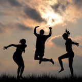 Silhouettes of friends jumping outdoor Stock Photos