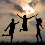 Silhouettes of friends jumping outdoor Stock Image