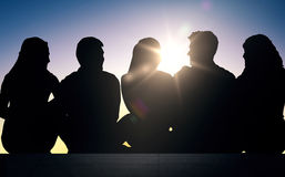 Silhouettes of friends sitting on stairs over sun Stock Images