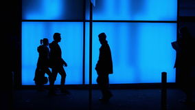 Silhouettes in front of blue glass wall