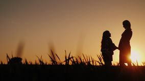 Silhouettes in full growth of mother and daughter. They stand in a picturesque place at sunset. Happy childhood concept royalty free stock image