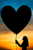 Silhouettes of a girl and balloon. Silhouettes of a girl holding heart balloon stock photo