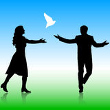 Silhouettes girl and guy released doves into the Royalty Free Stock Image