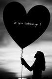 Silhouettes of a girl holding heart of sadness balloon.  royalty free stock images