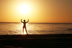 Silhouettes of the girl with the raised hands against a background of a sunrise. royalty free stock images