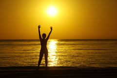 Silhouettes of the girl with the raised hands against a background of a sunrise on the sea coast. royalty free stock photos