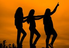 Silhouettes of girls against the sky at sunset, Royalty Free Stock Images