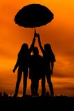 Silhouettes of girls against the sky at sunset,. Three silhouettes of girls against the sky at sunset, under one umbrella Stock Photos