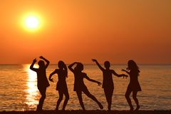 Silhouettes of girls dancing at the sunrise. On the beach stock photography