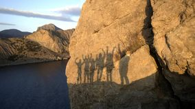 Silhouettes of a group of multiethnic friends waving their hands. Silhouette on a rock in the sea during sunset. Enjoy